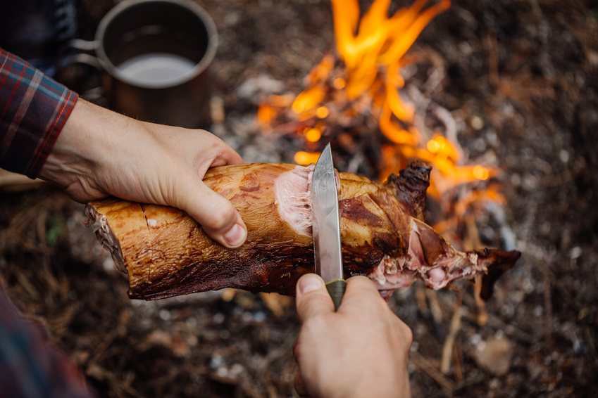 Man carving grilled rabbit meat in forest camp. Top view. Bushcraft concept