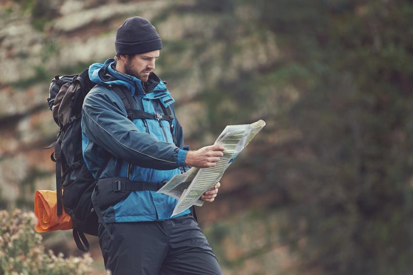 Man with map exploring wilderness on trekking adventure