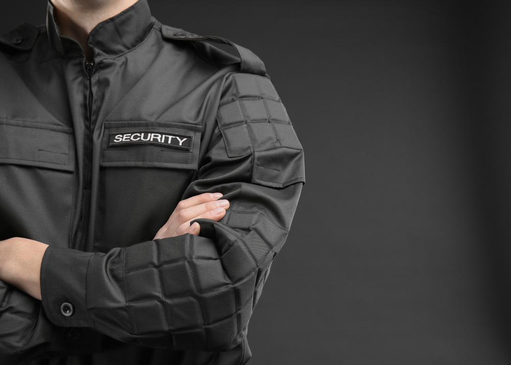 Jemand trägt eine schwarze Security-Jacke vor dunklem Hintergrund.