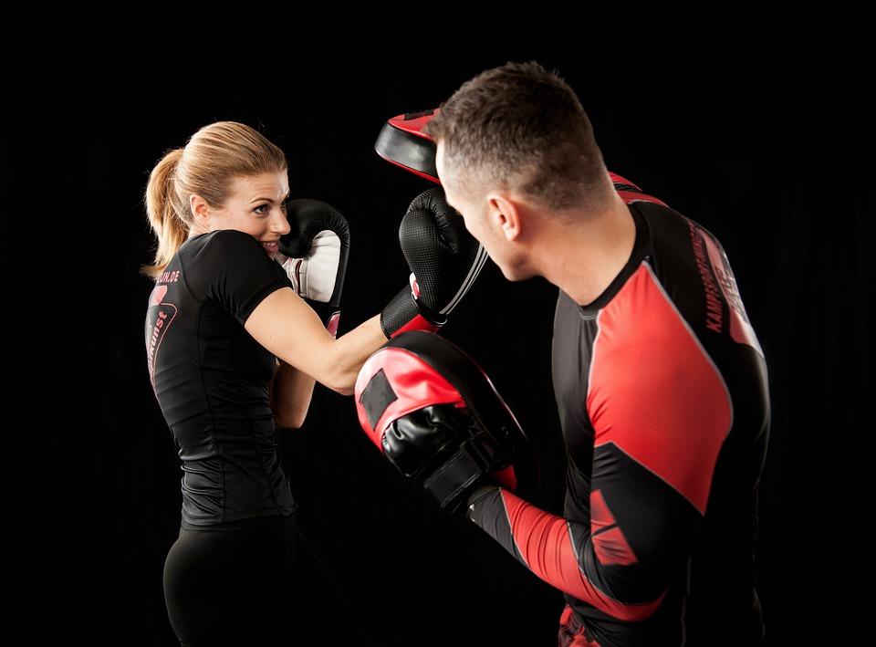 Eine junge Frau mit Boxhandschuhen vor schwarzem Hintergrund