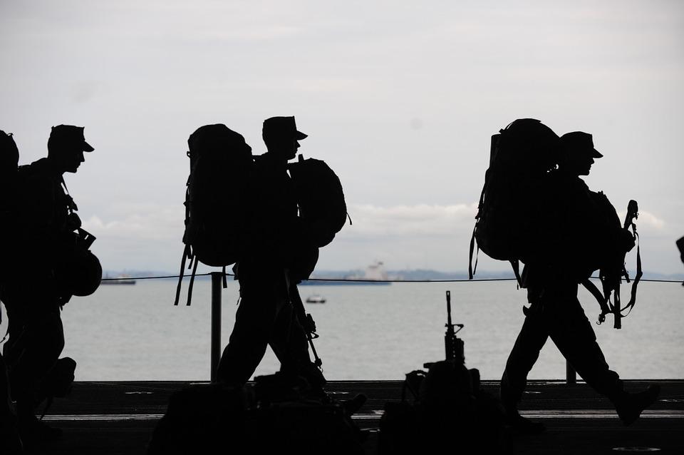 Drei Soldaten marschieren mit Rucksack